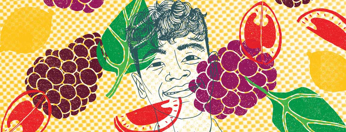 A young man with HIV smiling shown with colorful fruits and vegetables surrounding him