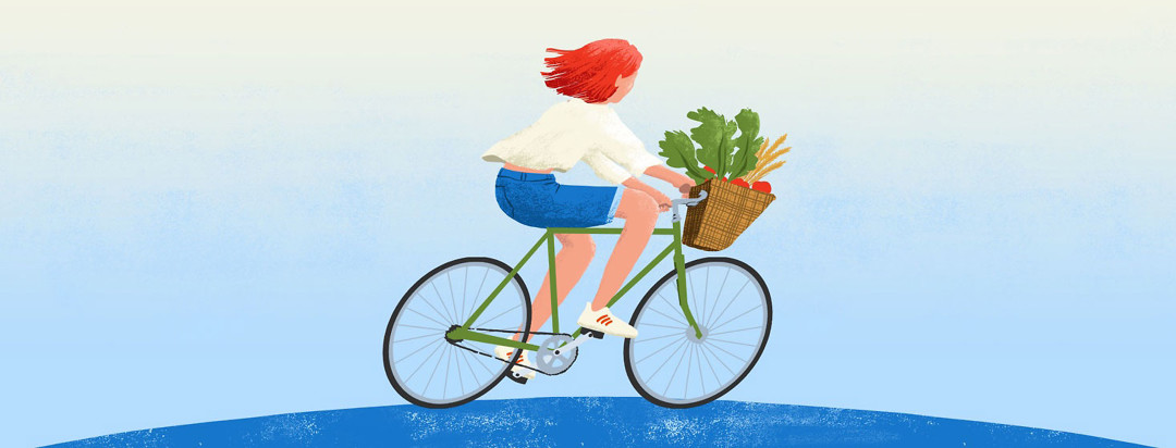 a woman riding her bike. Its basket is full of fresh vegetables
