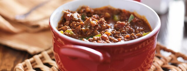 A bowl of chili with visible green pepper chunks sitting on a woven wicker pot holder in a red dutch oven.