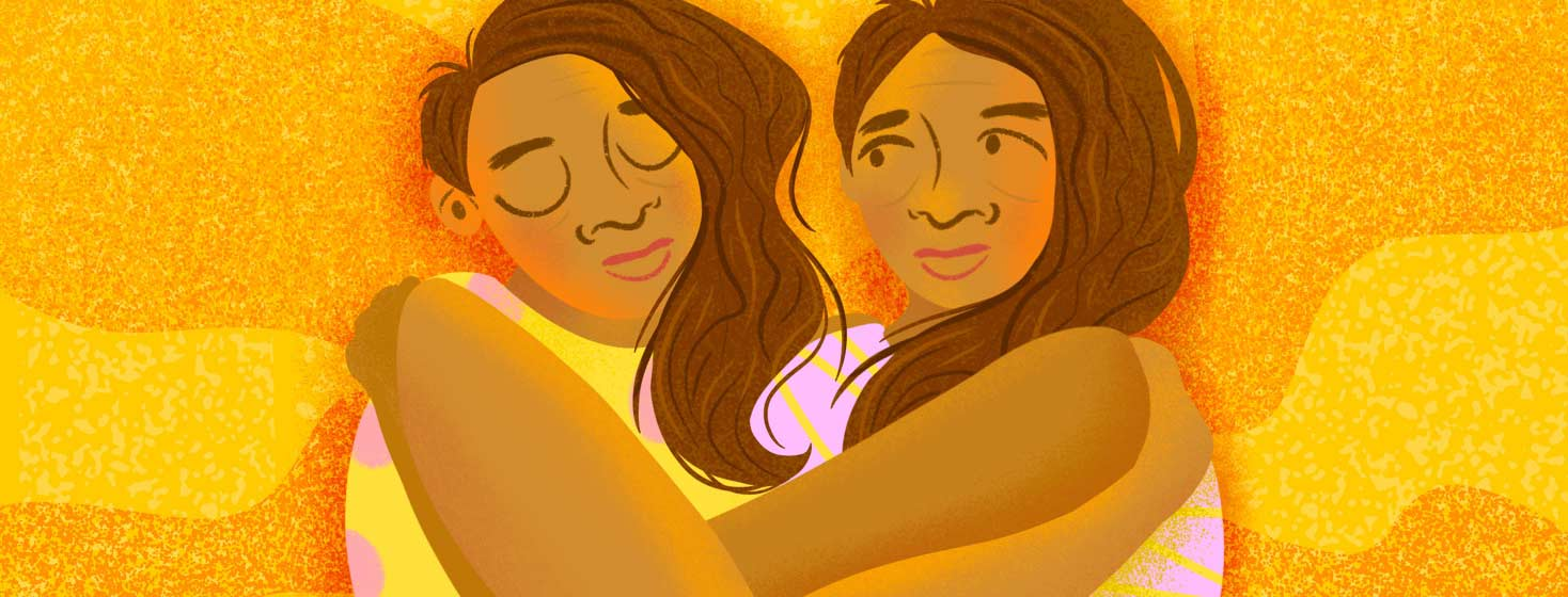 Two sisters tenderly embracing in a hug.